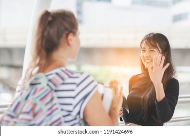 Multiethnic teenage greet and say hello or congratulating her friend colleague on birthday. Pretty student girl saying hello,smiling joyfully and friendly, waving her hand Having Fun Together Outdoors