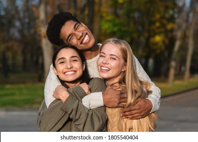 Multiethnic trio of friends guy and two girls hugging and smiling over park background, empty space