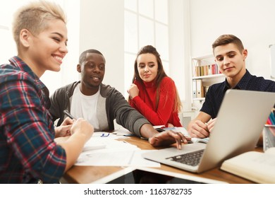 Multiethnic university students studying together. Young people working with tests and gadgets at wooden table. Education and technology concept, copy space