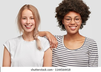 Multiethnic women with cheerful expressions laugh and have fun together, stand next to each other, dressed casually, isolated over white background. Interracial couple. Modern relations concept