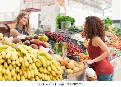 Multi-ethnic women trading organic veggies and fruits