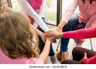 Multiethnic women wearing pink color clothes put their hands together in stack empowering each other in breast cancer awareness campaign meeting