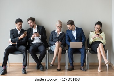 Multiethnic work applicants busy using laptops and smartphones preparing for recruiting talk, diverse job candidates sit in queue waiting for interview talking, browsing gadgets. Hiring, HR concept
