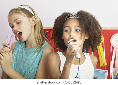 Multiethnic young girls using brushes as microphones to sing at a slumber party