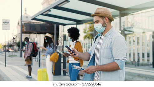 Multiethnic young males and females people im medical masks standing in line at bus stop. Keeping safe social distance. Caucasian stylish man tourist outdoors waiting for transport. Tourists.