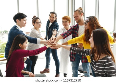 Multiethnic young team stack hands together as trusted unity and teamwork in modern office. Diverse group togetherness collaboration or friends huddle concept. Power of startup business team building.