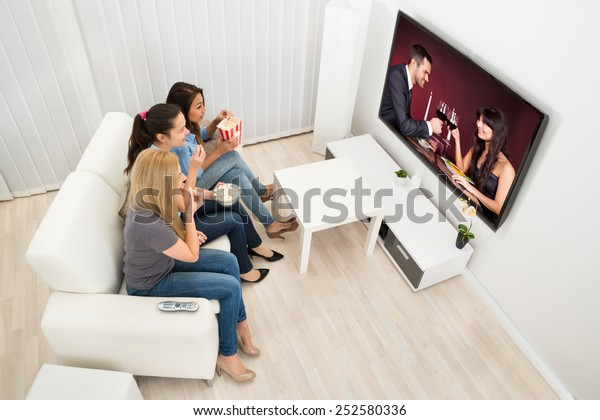 Multiethnic Young Women Sitting On Couch Watching Movie At Home