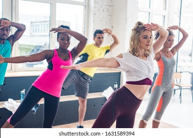 Multiethnic zumba dancers exercising in dance studio