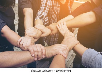 Multiethnic,ethnic group business people at the hands of a young businessman who is a symbol of their partnership and work as a strong team.volunteer putting their hands together on sunny day