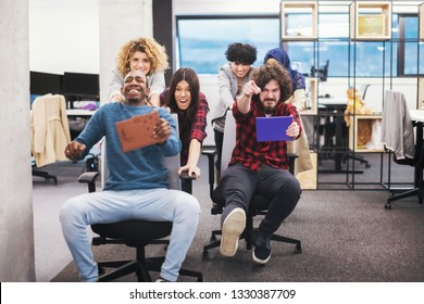multiethnics startup business team of software developers having fun while racing on office chairs,excited diverse employees laughing enjoying funny activity at work break