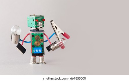 Multifunctional electrician robot with light bulbs and pliers in four hands. Colorful circuit board toy character holds different retro lamps. Funny electronic parts. copy space gray background