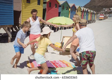 Multi-generated family playing at beach during sunny day