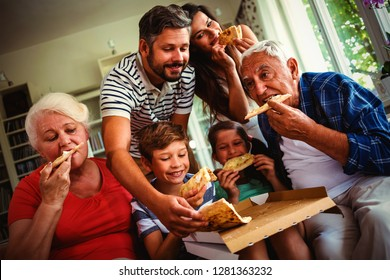 Multi-generation family eating pizza together at home