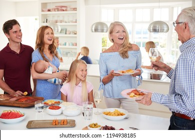 Multi-Generation Family And Friends Gathering In Kitchen For Celebration Party