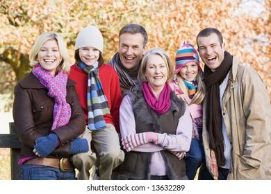 Multi-generation family on autumn walk sitting on fence