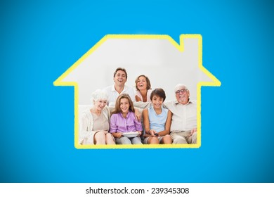 Multigeneration family on couch watching tv against blue background with vignette