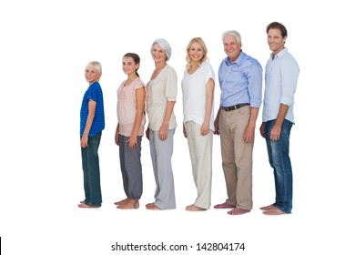 Multi-generation family posing together and looking at camera on white background