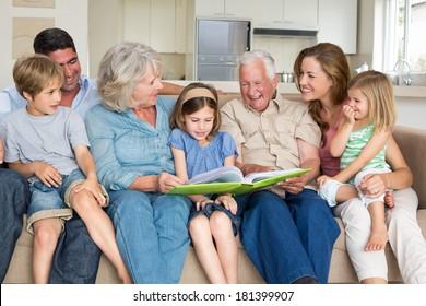 Multigeneration family reading storybook in living room