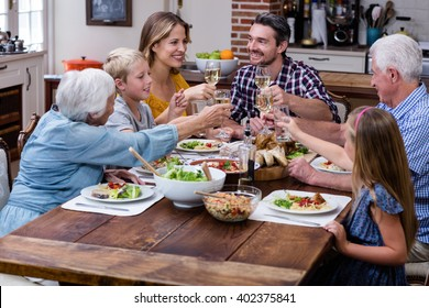 Multi-generation family toasting glass of wine while having meal - Shutterstock ID 402375841