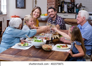 Multi-generation family toasting glass of wine while having mea - Shutterstock ID 402375871