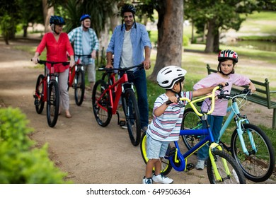 Multi-generation family walking with bicycle in park on a sunny day