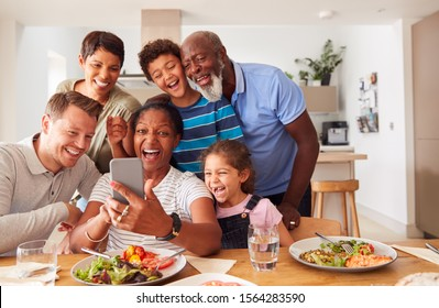 Multi-Generation Mixed Race Family Posing For Selfie As They Eat Meal Around Table At Home Together