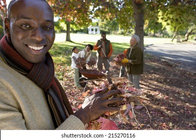 Multi-generational family collecting autumn leaves in garden, focus on father standing in foreground, portrait