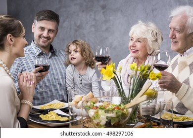 Multigenerational family at a dinner table drinking a toast to a young mother