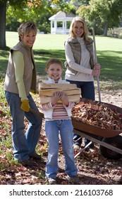 Multi-generational family doing yard work in autumn