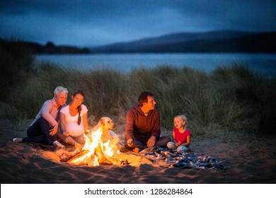 Multi-generational family enjoy a beach bonfire at night.