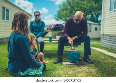 A multigenerational family is enjoying a barbecue in the trailer park