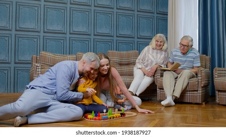 Multigenerational family leisure at home, couple grandpagents relaxing talking on sofa couch in living room and looking at kid child daughter playing with mother and father railway toy game on floor