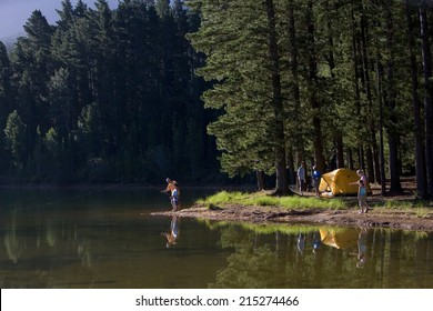 Multi-generational family on camping trip, boy (8-10) and grandfather fishing in lake in mid-distance, side view