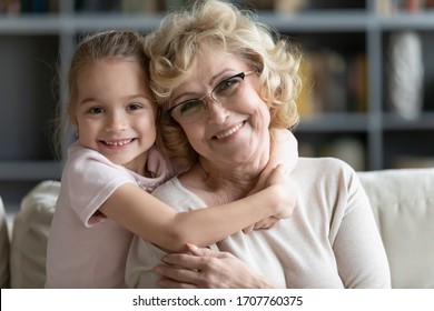 Multi-generational family portrait. Little granddaughter hugs grandma sit on sofa in living room smiling look at camera pose capture happy moment close up image, best friend gratitude for love concept