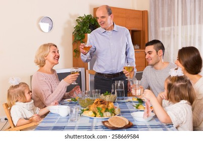 Multigenerational family sitting at the table set for dinner in the room