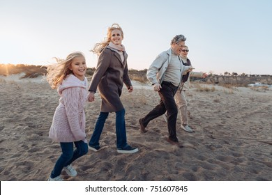 multigenerational family spending time together and walking on beach