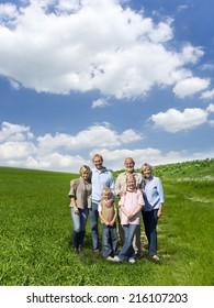 Multi-generational family standing in field