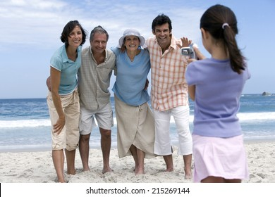 Multi-generational family standing on beach, girl (6-8) filming with camcorder, smiling