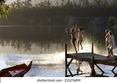 Multi-generational family standing on jetty at sunset, children (7-10) jumping into lake, side view