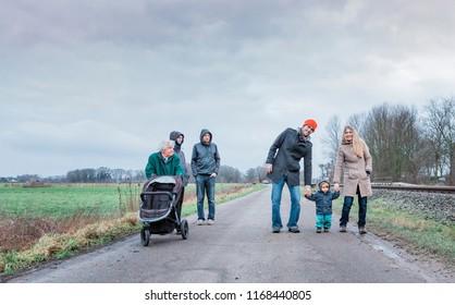 Multi-generational family walking on road between fields - Kempen, Germany, Europe