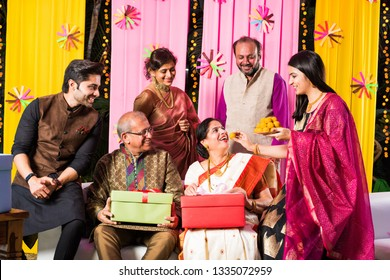 multigenerational Indian Family eating sweets while celebrating festival or occasion dressed in traditional wear, sitting on sofa/couch