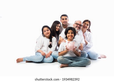 Multigenerational Indian family of six holding piggy bank while wearing white cloths and standing against white wall