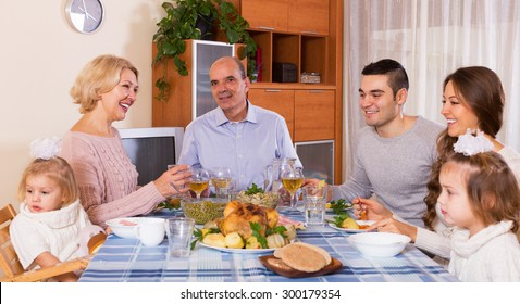 Multigenerational positive family having lunch together at room