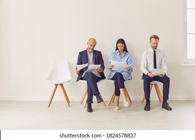 Multi-generational workforce. Three diverse applicants sitting in queue in office waiting for interview. Multiracial job seekers line up in corridor of business company. Copyspace