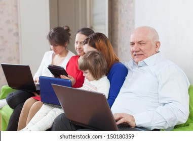 multigenerations family on sofa in livingroom  room with electronic devices at home