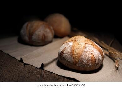 multigrain boule bread bakery on fabric wood table and dark background key light