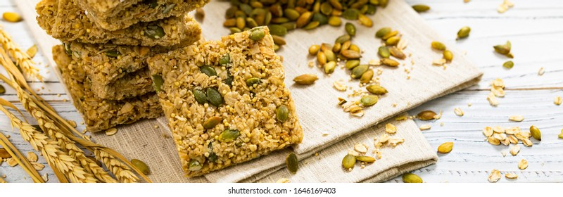 Multigrain Cereal Crunchy Squares Bars with Pumpkin Seeds on White Wooden Background. Healthy Snack. Selective focus.