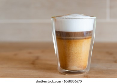 multilayer coffee or cappuccino in a glass cup on wooden table