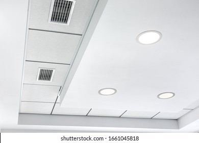 multi-level ceiling with three-dimensional protrusions and a suspended tiled ceiling with a built-in round led light and grille ventilation system.