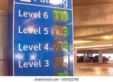 Multi-level garage smart guidance system with LED lighted numbers showing available or full spaces on each level. Intelligent indoor parking garage management